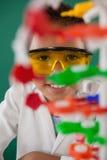 Усмехаясь модель молекулы школьника экспериментируя в лаборатории Стоковые Фотографии RF