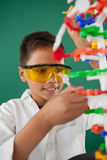Усмехаясь модель молекулы школьника экспериментируя в лаборатории Стоковое Изображение RF
