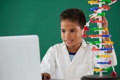 Усмехаясь модель молекулы школьника экспериментируя в лаборатории Стоковые Изображения