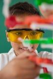 Усмехаясь модель молекулы школьника экспериментируя в лаборатории Стоковая Фотография