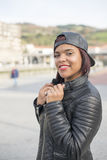 Усмехаясь молодая латинская женщина с бейсбольной кепкой в улице стоковые фото
