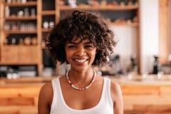 Усмехаясь молодая африканская женщина в кофейне стоковые изображения rf