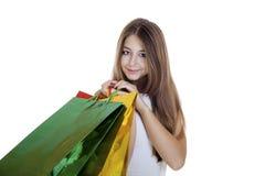 Усмехаясь молодая белокурая девушка с красочными хозяйственными сумками в белом d Стоковые Фото