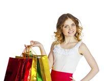 Усмехаясь молодая белокурая девушка с красочными хозяйственными сумками в белом d Стоковое Изображение