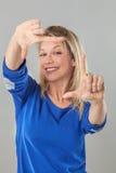 Усмехаясь молодая белокурая женщина делая рамку для фотографов Стоковое Фото