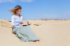 Усмехаясь молодая белокурая женщина читая книгу Стоковое Изображение RF