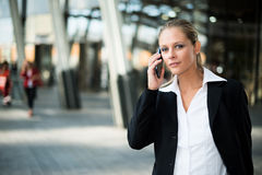 Усмехаясь молодая бизнес-леди говоря на телефоне стоковые фото
