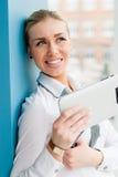 Усмехаясь молодая бизнес-леди используя ПК таблетки пока стоящ relaxed близко окно на ее офисе Стоковое фото RF