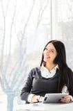 Усмехаясь молодая бизнес-леди используя ПК таблетки пока стоящ relaxed близко окно на ее офисе Стоковое Изображение