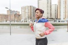 Усмехаясь молодая женщина бежать в улице стоковое изображение rf