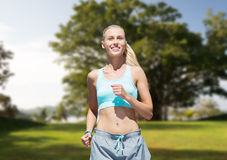 Усмехаясь молодая женщина бежать или jogging над парком Стоковая Фотография RF