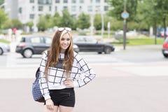 Усмехаясь молодая женщина битника с рюкзаком в смотреть улицы стоковые изображения rf
