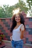 Усмехаясь молодая женщина брюнет представляя в дворе стоковые фотографии rf
