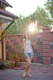 Усмехаясь молодая женщина брюнет представляя в дворе Стоковые Фото