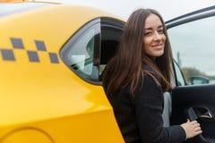 Усмехаясь молодая женщина брюнет представляя от классического желтого такси стоковое изображение