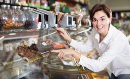 Усмехаясь молодая женщина выносить самый лучший десерт Стоковое фото RF