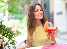Усмехаясь молодая женщина выпивая коктеиль Стоковые Фотографии RF