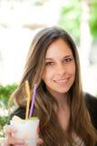 Усмехаясь молодая женщина выпивая коктеиль Стоковое Фото