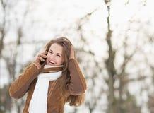 Усмехаясь молодая женщина в мобильном телефоне парка зимы говоря Стоковые Фотографии RF