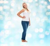 Усмехаясь молодая женщина в пустых белых рубашке и джинсах Стоковое Изображение
