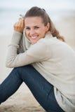 Усмехаясь молодая женщина в свитере сидя на сиротливом пляже Стоковое Изображение RF