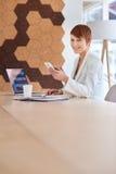 Усмехаясь молодая женщина в современных размерах офиса с телефоном Стоковое Изображение