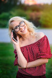 Усмехаясь молодая женщина в стеклах с телефоном outdoors Стоковое Изображение