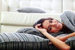 Усмехаясь молодая женщина лежа на поле с подушками Стоковое Фото