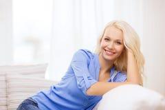 Усмехаясь молодая женщина лежа на софе дома Стоковые Изображения