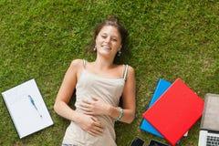 Усмехаясь молодая женщина лежа на траве с книгами Стоковое фото RF