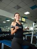 Усмехаясь молодая женщина держа гантели в спортзале Стоковое Изображение