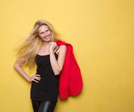 Усмехаясь молодая женщина держа куртку стоковая фотография