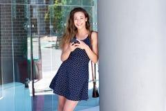 Усмехаясь молодая женщина держа мобильный телефон снаружи Стоковые Изображения RF
