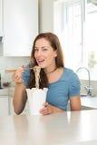 Усмехаясь молодая женщина есть лапши в кухне Стоковые Изображения