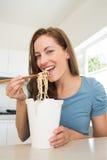 Усмехаясь молодая женщина есть лапши в кухне Стоковые Фотографии RF