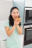 Усмехаясь молодая женщина есть кусок пиццы в кухне Стоковые Фотографии RF