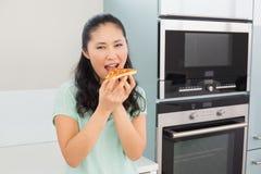Усмехаясь молодая женщина есть кусок пиццы в кухне Стоковая Фотография RF