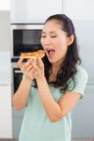 Усмехаясь молодая женщина есть кусок пиццы в кухне Стоковое фото RF