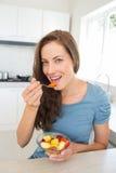 Усмехаясь молодая женщина есть фруктовый салат в кухне Стоковая Фотография