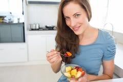 Усмехаясь молодая женщина есть фруктовый салат в кухне Стоковые Изображения RF