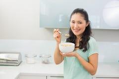 Усмехаясь молодая женщина есть хлопья в кухне Стоковые Изображения