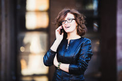 Усмехаясь молодая женщина используя передвижной smartphone Стоковые Фотографии RF