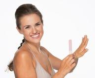 Усмехаясь молодая женщина используя пилочку для ногтей Стоковая Фотография RF