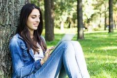 Усмехаясь молодая женщина используя цифровую таблетку стоковое изображение rf