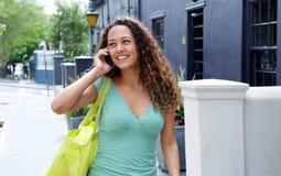 Усмехаясь молодая женщина идя и говоря в городе Стоковая Фотография