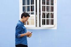 Усмехаясь молодая женщина идя снаружи с мобильным телефоном Стоковая Фотография