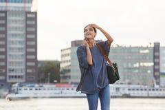 Усмехаясь молодая женщина идя с сумкой и говоря на сотовом телефоне Стоковые Фотографии RF