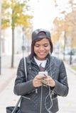 Усмехаясь молодая женщина моды с наушниками слушая к музыке и идя в улицу стоковое изображение