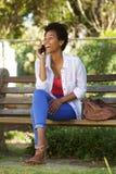 Усмехаясь молодая женщина на скамейке в парке используя сотовый телефон Стоковая Фотография RF