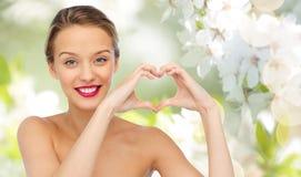 Усмехаясь молодая женщина показывая знак руки формы сердца Стоковые Фотографии RF